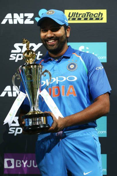 Rohit Sharma of India holds the series trophy after